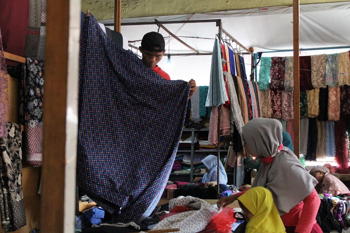 Penjual mengukur lebar kain yang hendak dibeli sementara seorang pengunjung memilih-milih barang di lapaknya pada Minggu (15/11). Banyak pengunjung yang membawa serta anak kecil, membuat suasana pasar semakin ingar-bingar.