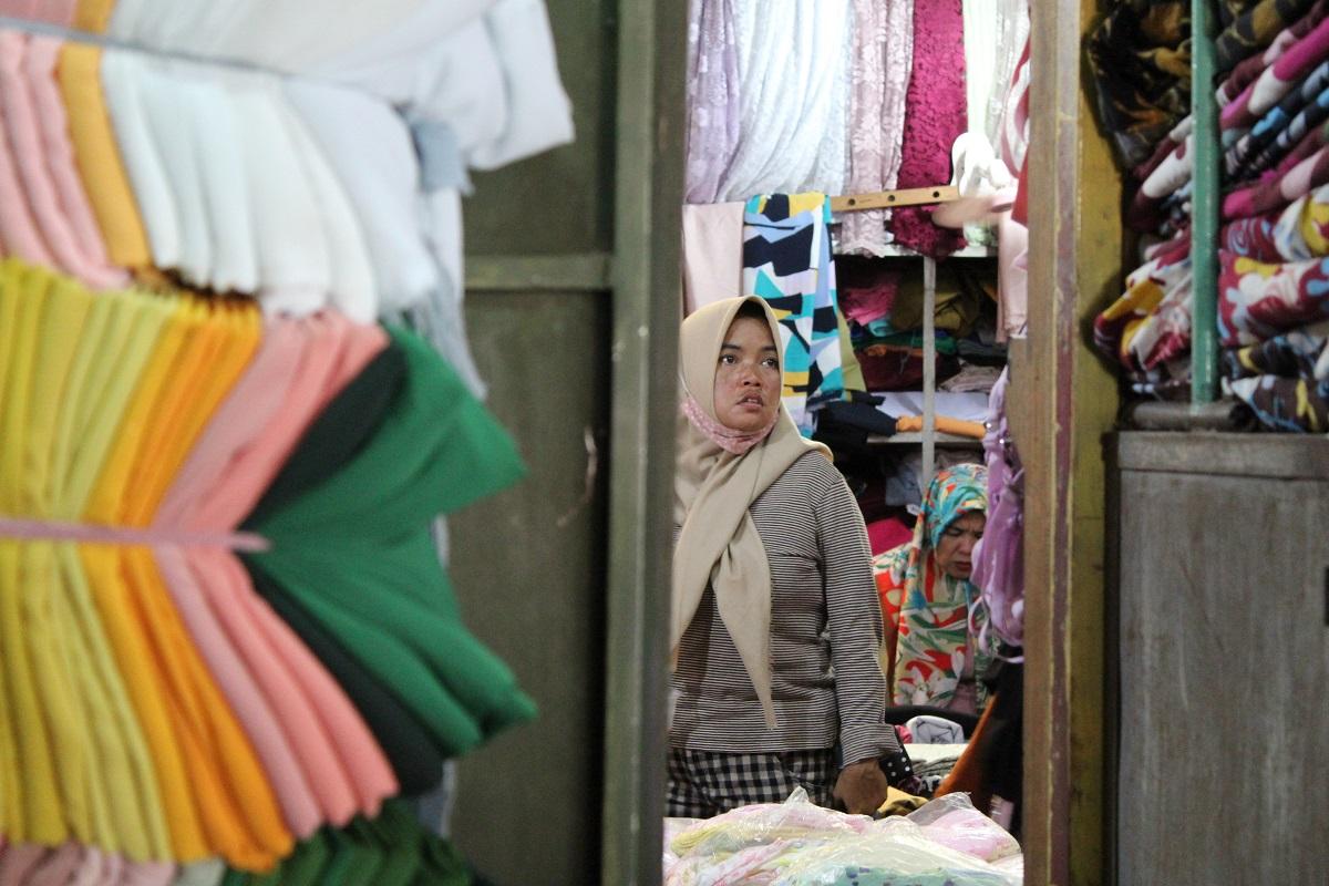 Seorang pengunjung Pasar Pagi Kota Tegal mengamat-amati kain di salah satu lapak pedagang pada Minggu (15/11). Kebanyakan pembeli mencari ragam kain katun seperti rayon, toyobo, katun jepang, dan katun madinah.